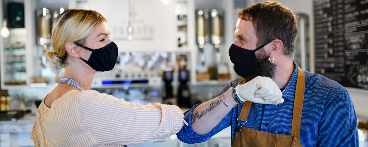 Portrait of coffee shop owners with face masks elbow bumping, open after lockdown quarantine, coronavirus concept.