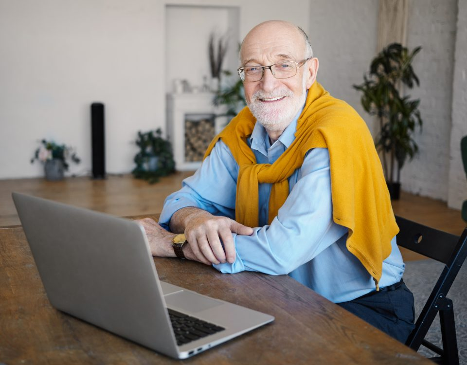 Indoor shot of handsome positive unshaven sixty year old man writer wearing eyeglasses and stylish clothes working distantly sitting at desk in front of open laptop computer, smiling broadly at camera